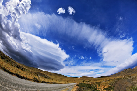 glisten: Gray dirt road in the Chile National Park Torres del Paine. Incredible shaped clouds formed by glaciers glisten in the sun. Picture taken with a fisheye lens Stock Photo
