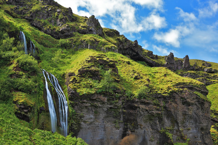 day flowering: Selyalandfoss waterfall and picturesque flowering fields. Iceland in July. Warm summer day