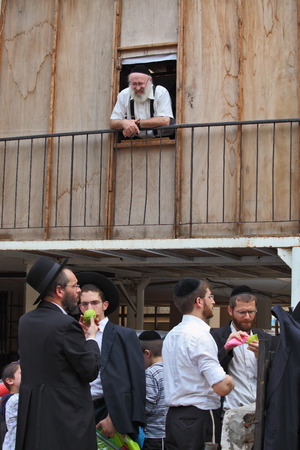 jewish group: Bnei Brak - September 22: Picturesque scene: A group of young religious Jews in black velvet skullcaps on the market to choose citron Sukkot. An elderly white-bearded rabbi with a smile watching them September 22, 2010 in Bnei Brak, Israel Editorial
