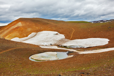 hollows: July in Iceland. Smoldering underground heat hillsides. In the hollows are last years snow fields Stock Photo