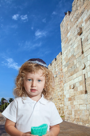 sukkot: Cute little boy with long blond curls and blue eyes in knitted skullcap. He stands at fortress walls of Old City of Jerusalem. The Jewish holiday of Sukkot Stock Photo