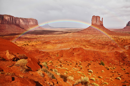 indian tribe: Certain rocks - mitts are crossed with a picturesque rainbow. Red stone desert of an Indian tribe of the Navajo, USA