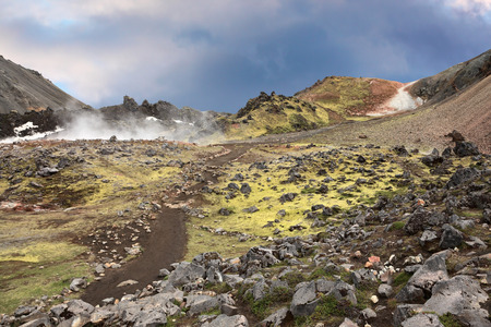 smoldering: Rhyolite mountains smoldering underground heat. In the hollows lie unmelted snow patches from last year