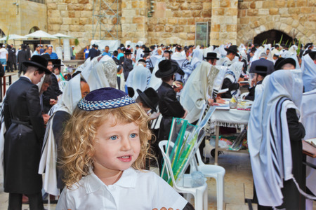 skullcap: Adorable little boy with long blond curls and blue eyes in knitted skullcap. He stands at Western Wall of Temple. The Jewish holiday of Sukkot Editorial