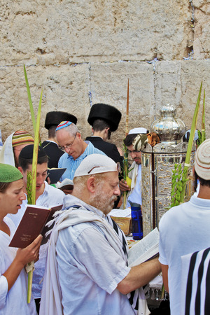 sukkoth festival: JERUSALEM, ISRAEL - SEPTEMBER 20, 2013: The Western Wall of the Temple in Jerusalem. Many religious Jews in traditional white robes tallit gathered for prayer. Morning Sukkot
