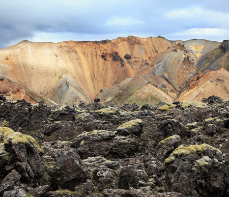 hollows: National Park Landmannalaugar in Iceland. Pieces of gray and black lava, sometimes covered with green moss. In the background - blue and orange rhyolite mountains Stock Photo