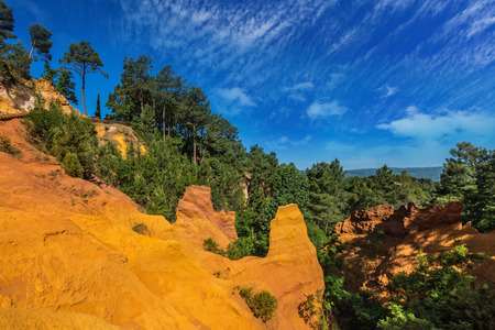ocher: Multi-colored ocher outcrops - from yellow to orange-red. Green trees create a beautiful contrast with the ocher. Roussillon, Provence Red Village