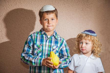 etrog: The Jewish holiday of Sukkot. Two boys in yarmulkes. The older boy is holding the etrog