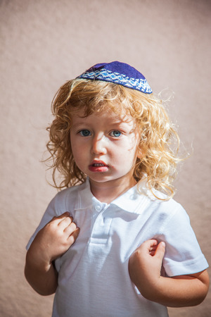 kippah: The charming little boy with long blond curls and blue eyes in Jewish knitted kippah