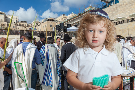 skullcap: Cute little boy with long blond curls and blue eyes in blue skullcap. He stands at Western Wall of Temple. The Jewish holiday of Sukkot