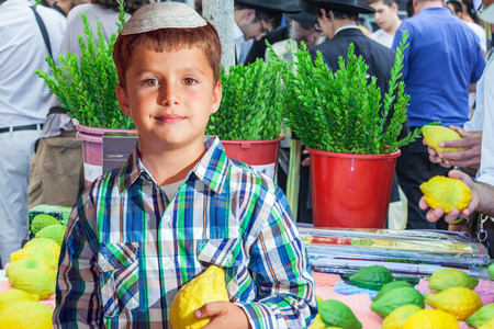 etrog: The Jewish holiday of Sukkot. Seven year old boy in white skullcap with etrog. He stand  on a pre-holiday market in Jerusalem. Ritual plants - myrtle prepared for sale