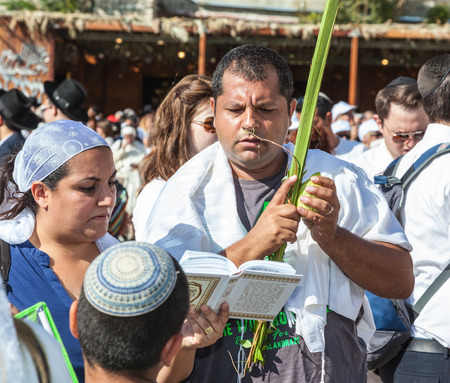 sukkoth: JERUSALEM, ISRAEL - OCTOBER 12, 2014: The area in front of Western Wall of Temple filled with people.  Many believers have brought prayer books and four ritual plants. Morning autumn Sukkot