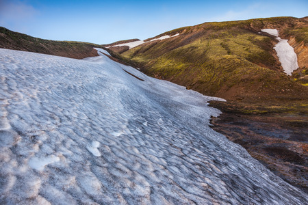 snowfield: Summer morning in the National Park Landmannalaugar, Iceland. Big unmelted in July snowfield Stock Photo