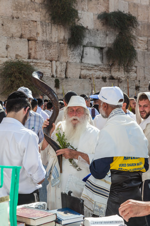 JERUSALEM, ISRAEL - OCTOBER 12, 2014: Morning autumn Sukkot. The area in front of Western Wall of  Temple filled with people. Elderly religious Jew with a Shofar