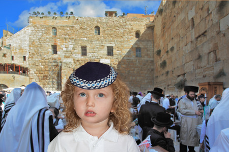 western wall: The lovely little boy with long light curls and blue eyes in a knitted skullcap. It costs at the main Jewish shrine - the Western wall of the Temple. Jewish holiday of Sukkot