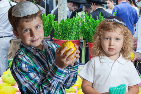 etrog: The Jewish holiday of Sukkot. Cute little boy with long blond hair in  knitted skullcap and  seven year old boy in white skullcap with etrog. They stand  on a pre-holiday market in Jerusalem. Ritual plants - myrtle prepared for sale