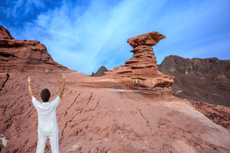 pinnacle: The woman - tourist in a white suit for yoga delighted raised her hands. Warm January day. The mountains of pink sandstone