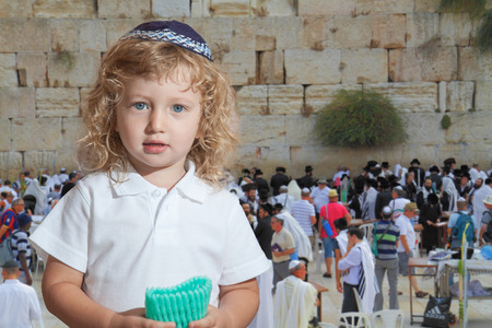 skullcap: Cute little boy with long blond curls and blue eyes in knitted skullcap. He stands at the main Jewish shrine - Western Wall of Temple. The Jewish holiday of Sukkot Editorial