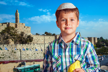 seven year old: Charming seven year old boy in white festive skullcap with etrog. Sukkot in Jerusalem