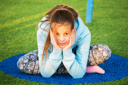 teenage girl: Family childrens party. Beautiful teenage girl is engaged in yoga on the playground Stock Photo
