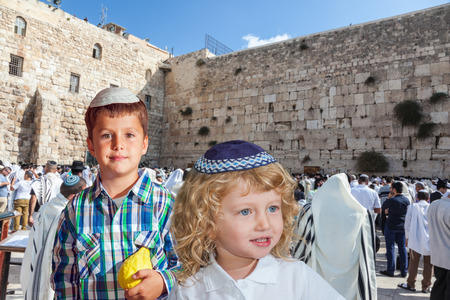 sukkot: Cute little boy in a skullcap and his older brother seven years. They cost at Western Wall of Temple. The Jewish holiday of Sukkot