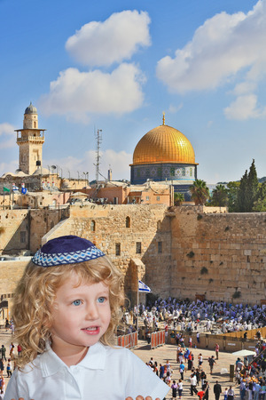 skullcap: The Jewish holiday of Sukkot. Cute little boy with long blond curls and blue eyes in knitted skullcap. He stands at the main Jewish shrine - Western Wall of Temple Editorial