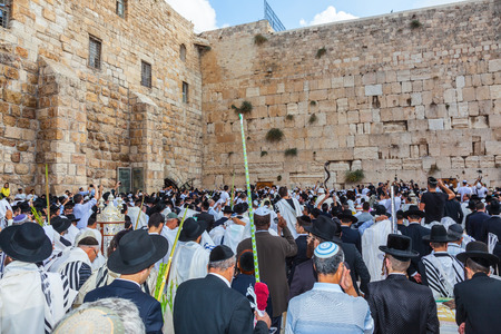 sukkoth: JERUSALEM, ISRAEL - OCTOBER 12, 2014:  Morning autumn Sukkot. Crowd of Jewish worshipers in white wearing prayer shawls. The area of Western Wall of  Temple filled with people