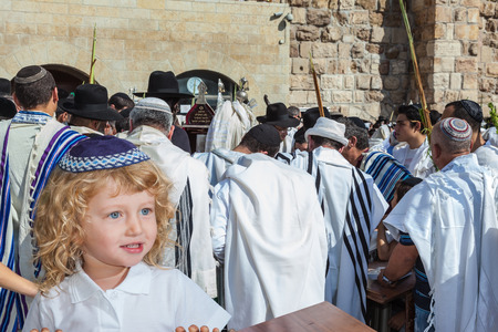 yarmulke: Adorable little boy with long blond curls and blue eyes in blue skullcap. He stands at Western Wall of Temple. The Jewish holiday of Sukkot