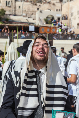 talmud: JERUSALEM, ISRAEL - OCTOBER 12, 2014: The area in front of Western Wall of  Temple filled with people.   Young boy in tallit praying. Morning autumn Sukkot