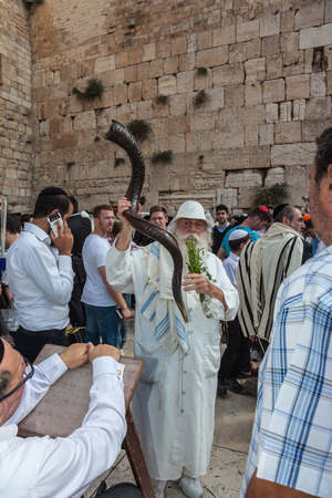 holies: JERUSALEM, ISRAEL - OCTOBER 12, 2014: Morning autumn Sukkot. The area in front of Western Wall of  Temple filled with people. Elderly religious Jew with a Shofar
