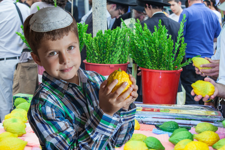 seven year old: The Jewish holiday of Sukkot,  Holiday market in Jerusalem. Seven year old boy in white skullcap with etrog. Ritual plants - myrtle prepared for sale