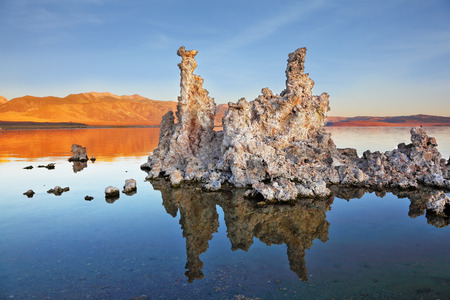 calcareous: The magic of Mono Lake. Outliers - bizarre limestone calcareous tufa formation reflected in the smooth water. Orange sunset Stock Photo