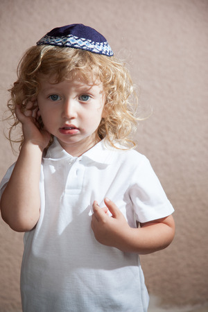 kippah: Autumn holiday of Sukkot. The charming little boy with long blond curls and blue eyes in the Jewish knitted yarmulke