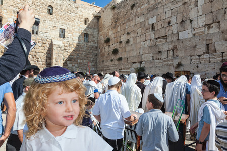 skullcap: The Jewish holiday of Sukkot. Adorable little boy with long blond curls and blue eyes in blue skullcap. He stands at Western Wall of Temple