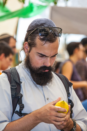 sukkoth festival: JERUSALEM, ISRAEL - OKTOBER 8, 2014: Traditional market before the holiday of Sukkot.  Religious Jew with black beard very carefully examines ritual citrus - etrog