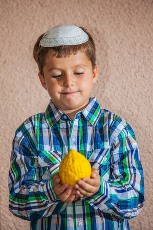 sukkoth: Etrog -  ritual fruit for the Jewish holiday of Sukkot. Beautiful seven year old boy in white knitted skullcap is holding citron