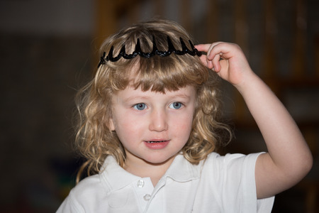 blue eyes: The charming little boy with blue eyes and blond curls in toy crown