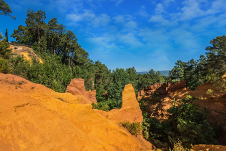 ocher: Roussillon, Provence Red Village.  Multi-colored ocher outcrops - from yellow to orange-red. Green trees create a beautiful contrast with the ocher