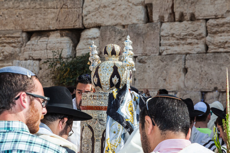 worshipers: JERUSALEM, ISRAEL - OCTOBER 12, 2014: Morning autumn Sukkot. The area in front of Western Wall of  Temple. Crowd of Jewish worshipers in white wearing prayer shawls. On table there is Torah Roll in magnificent case