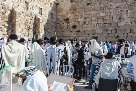 holies: JERUSALEM, ISRAEL - OCTOBER 12, 2014:  Huge crowd of faithful Jews wearing white prayer shawls and black long-skirted coats. Morning Sukkot