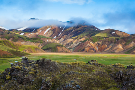 hollows: Snow and fog lies in the hollows of colorful rhyolite mountains. Green Valley is flooded with melt water. Summer morning in the National Park Landmannalaugar, Iceland Stock Photo