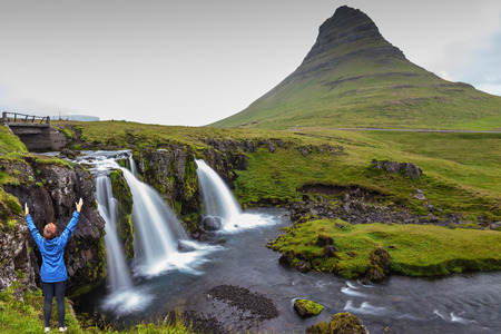 admires: Threaded full-flowing waterfall Kirkjufell Foss on the grassy mountains. Middle-aged woman tourist admires the beauty of nature Stock Photo