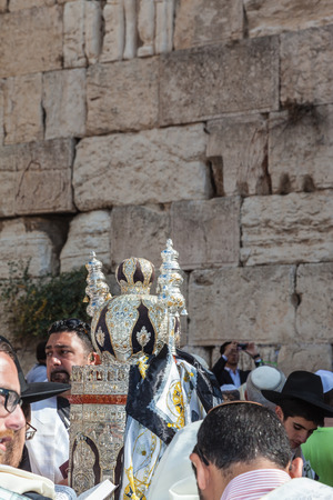 talmud: JERUSALEM, ISRAEL - OCTOBER 12, 2014: Morning autumn Sukkot. The area in front of Western Wall of  Temple. Crowd of Jewish worshipers in white wearing prayer shawls. On table there is Torah Roll in magnificent case