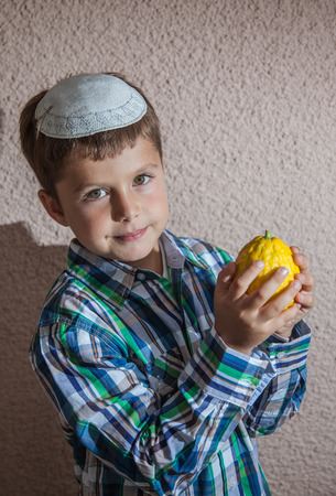 sukkoth: Very beautiful seven year old boy in white knitted kippah is holding citrus.  Etrog  -  ritual fruit for Sukkot