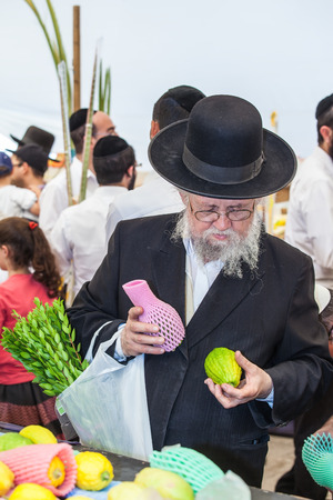 sukkoth: JERUSALEM, ISRAEL - OKTOBER 8, 2014: Traditional market before the holiday of Sukkot. Orthodox Jew with a white beard in a black hat chooses citrus Editorial