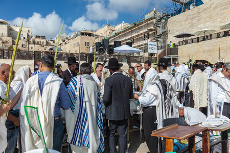 lulav: JERUSALEM, ISRAEL - OCTOBER 12, 2014:  Morning autumn Sukkot. Crowd of Jewish worshipers in white wearing prayer shawls. The area of Western Wall of  Temple filled with people