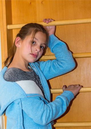 wall bars: Family childrens party. Older sister posing near the wall bars