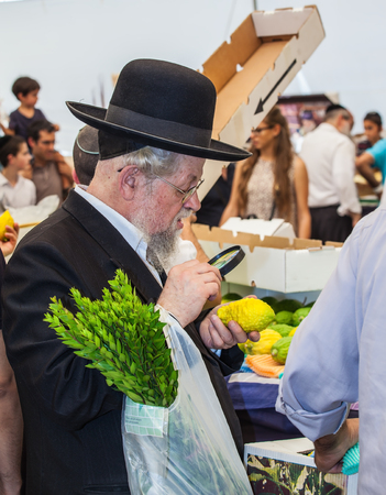 he is a traditional: JERUSALEM, ISRAEL - OKTOBER 8, 2014: Traditional market before the holiday of Sukkot. Orthodox Jew with a white beard in a black hat chooses citrus - etrog. He checks with  magnifying glass each fruit