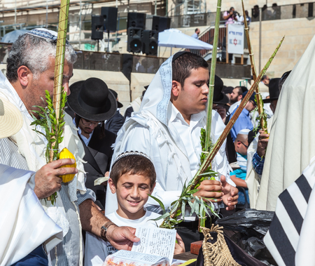 holies: JERUSALEM, ISRAEL - OCTOBER 12, 2014: Morning autumn Sukkot. The area in front of the Western Wall of the Temple filled with people. Many brought prayer books and four ritual plants