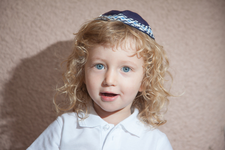 jewish ethnicity: The charming little boy with blue eyes and long blond curls in Jewish knitted skullcap. Autumn holiday of Sukkot